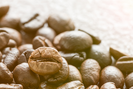 Close up heap of roasted brown coffee beans with sunlight