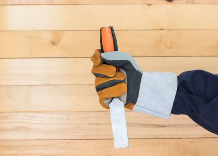 Working hand in glove holding a chisel with wall wood background Stock Photo