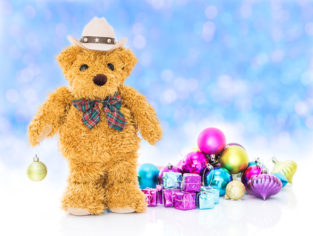Teddy bear with gifts and ornaments christmas and new year on blue bokeh background