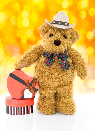 Teddy bear with  Red heart shaped gift box on yellow bokeh background Stock Photo
