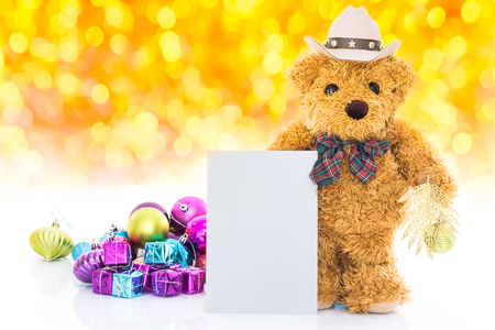 GLOD: Teddy bear with gifts and blank greeting card on yellow background