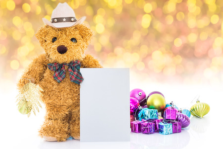 Teddy bear with gifts and blank greeting card on yellow background