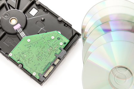 Hard disk drive (HDD) with circuit board and dvd discs on white background Stock Photo