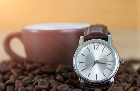 Coffee time concept ,Close up of roasted brown coffee beans on wood tray and wrist watch with coffee cup