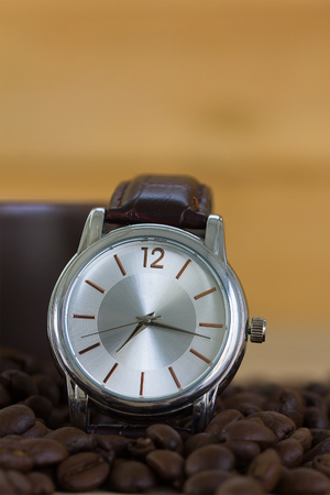 Coffee time concept ,Close up of roasted brown coffee beans in wood tray and wristwatch with coffee cup