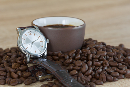 Coffee time concept ,Close up roasted brown coffee beans in wood tray and wristwatch with coffee cup