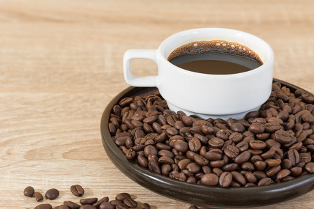 Close up roasted brown coffee beans in wood tray and coffee cup