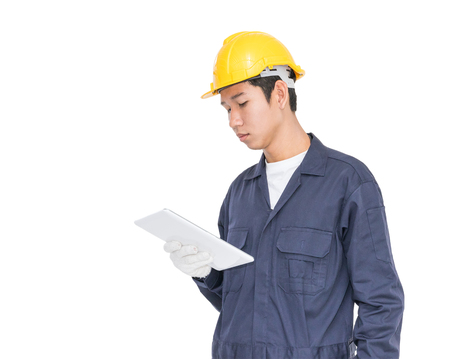 architect: Young worker with yellow helmet using a tablet holding blueprint isolated over white background