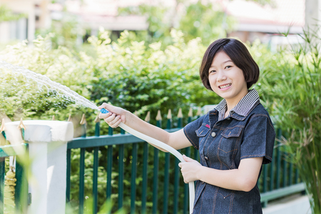 Asian women standing Spraying a tree in garden at her house