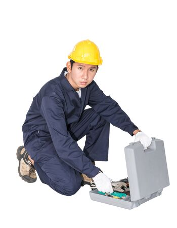 Young handyman sitting with his tool box isolated on white background Stock Photo