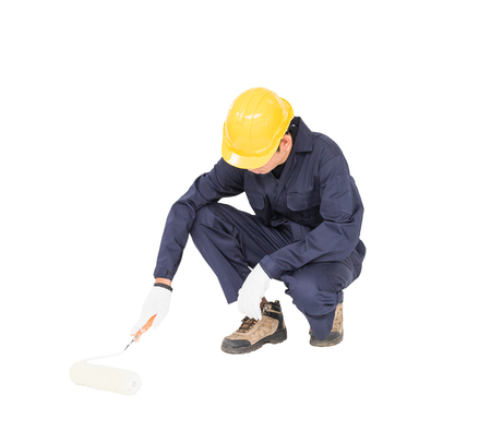 Young worker in a uniform using a paint roller is painting invisible floor, isolated on white background cutout Stock Photo