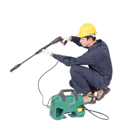 Young man in uniform sitting and holding high pressure water gun portable with hose, Cut out isolated on white background