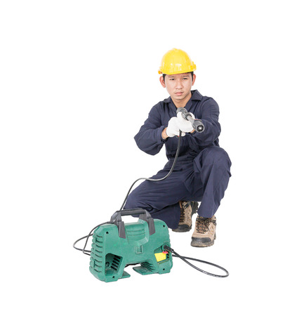 Young man in uniform sitting and holding high pressure water gun portable with hose, Cut out isolated on white background Stock Photo