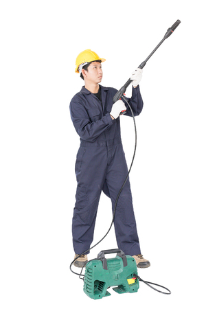 Young man in uniform stand and holding high pressure water gun portable with hose, Cut out isolated on white background Stock Photo