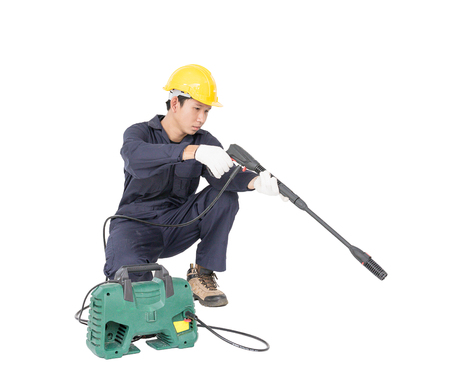 Young man in uniform sitting and holding high pressure water gun portable with hose, Cut out isolated on white background Reklamní fotografie