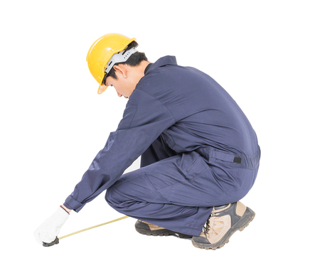 Young worker in unifrom with tape measure isolated on white background cutout Stock Photo