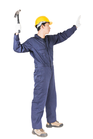 obrero: Young handyman in uniform standing with his hammer, Cutout isolated on white background Foto de archivo