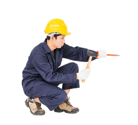 clavados: Young man in uniform sit and holding hammer was nailed to a cold chisel, Cut out isolated on white background