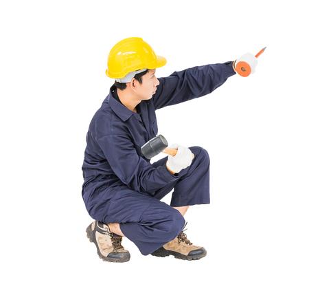 clavados: Joven en uniforme sentarse y la celebración de martillo fue clavado en un cincel frío, Cortar aislado sobre fondo blanco