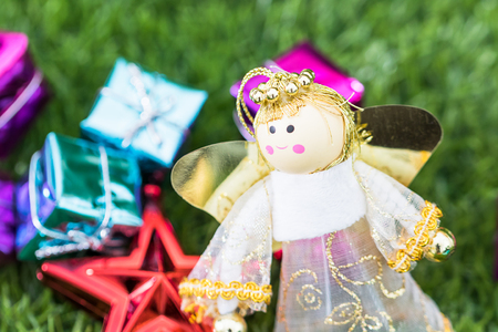 Celebration of New year and Christmas, Christmas angel doll and christmas decoration on green grass background Stock Photo