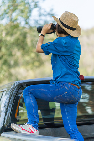 Close up Young asian woman short hair wear hat and hold binocular in grass field countryside Thailand Stock Photo