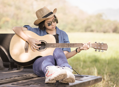 Young asian women short hair wear hat and sunglasses playing guitar ,sit on pickup truck in countryside Thailand Stock Photo