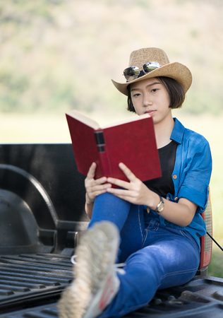 Young asian women short hair wear hat and sunglasses read a book ,sit on pickup truck in countryside Thailand