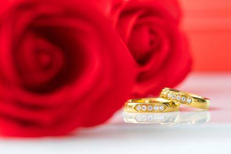 Rode plastic valse rozen op witte achtergrond, Huwelijksconcept met rozen en gouden ringen