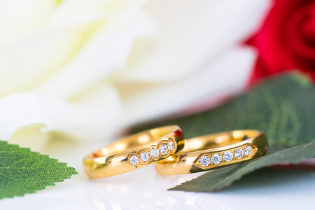 Close up Gold ring and Red roses on white  background, Wedding concept with roses and gold rings Stock Photo