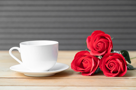Red rose and coffee cup on wood background, Valentine concept