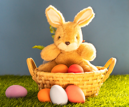 Easter bunny toy and Easter eggs in basket on green grass Stock Photo