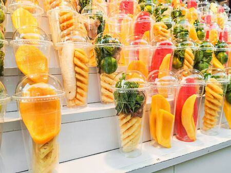 Mix fruits in a plastic glass on wooden shelves prepare for make smoothie juice at street market Imagens