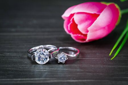 Close up Diamond gem wedding rings with pink tulip flower on black background Stock Photo