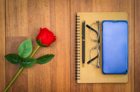 Top view image of notebook and cellphone with red rose on wooden table background Archivio Fotografico