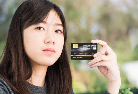 Close up young woman holding credit card. Online shopping concept