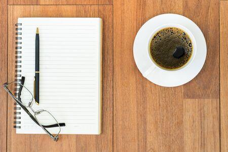 Bovenaanzicht bril en pen op notitieblok en koffiekopje op houten dek met kopieerruimte