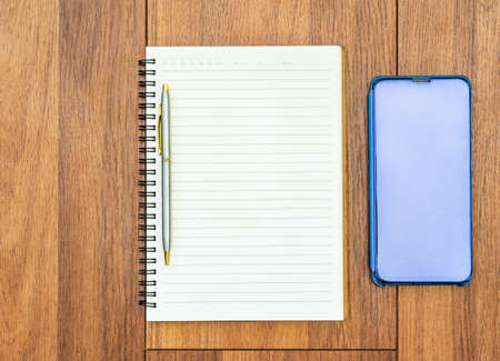 Top view image of open notebook with blank pages and cellphone on wooden table background for adding text or mockup Stockfoto