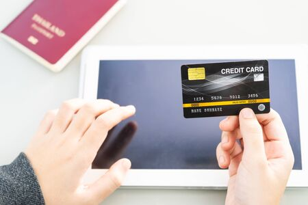 Close up of Female hand hold credit card with tablet computer blank copy space screen  ,Online Travel Booking Concept