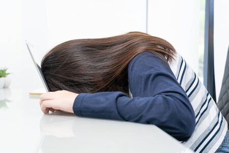 Young woman long hair tired from studying online and fall asleep on desk with laptop Foto de archivo