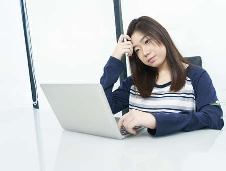 Young female student sitting in living room using laptop at desk learning online