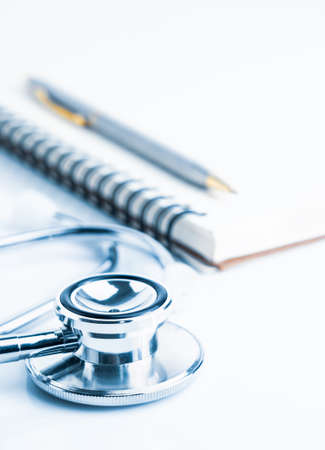 Close up Medical stethoscope with blank notepad as medical concept