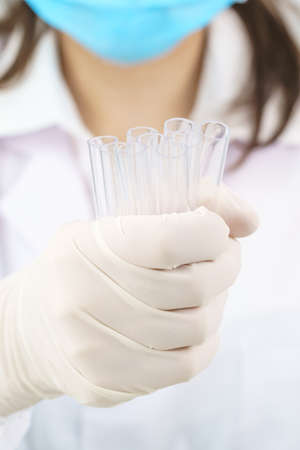 Technician scientist analyzing a blood sample in test tube in laboratory for testing it on COVID, COVID-19, coronavirus virus analysis Banco de Imagens