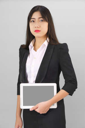 Young women standing in suit holding her digital tablet computor