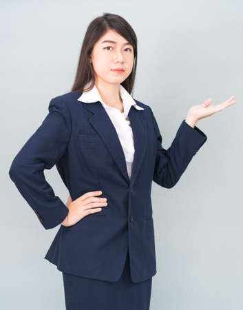 Asian woman in suit open hand palm gestures with empty space isolated on gray background
