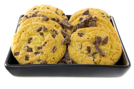 A picture of two stacks of some chocolate cookies with some chocolate on a black plate