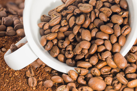 espesso: Picture of a white cup filled with coffee beans