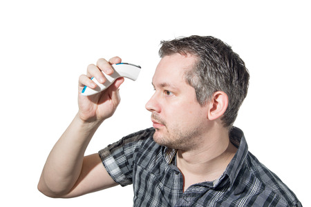 Picture of a man that is checking his temperature the modern way