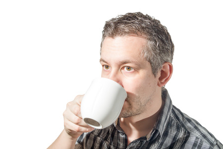 Picture of a man that is drinking coffee from a white cup