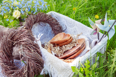 Wooden hearts and plates lie in a basket with braided wreaths made of branches on a picnic. decorations photo
