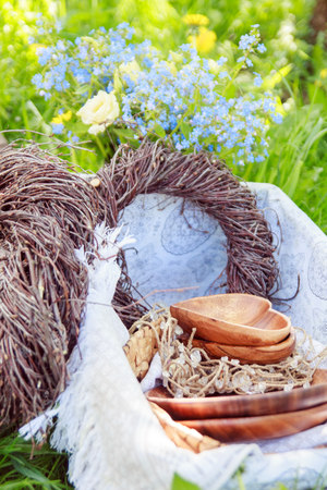 decorations wreaths: Wooden hearts and plates lie in a basket with braided wreaths made of branches on a picnic. decorations Stock Photo